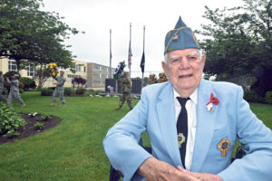 "Catholic War Veterans member Pete Johnson of Hicksville served with the U.S. Navy from 1948-52, spending time on the destroyer Myles C. Fox (""[Serial number] DDR-829,"" he quickly added). Behind him, members of the U.S. Army 333rd Military Police Brigade carry the wreaths from the Veterans Memorial Park to the post-parade ceremony. (Photo by Frank Rizzo)"