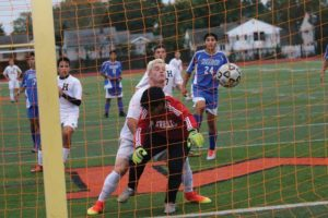 Hicksville's Matt Sloan pressures Herricks goalie Cleber Guamann in the Sep. 28 game. Guamann could not hold on to this direct kick by Storm Strongin in Hicksville's 1-0 win. Hicksville's Michael Constantinescu (left) and Jason McMullan (just over Sloan's shoulder) watch, along with Herrick's Luke Laurino (24).           (Photo by Frank Rizzo)