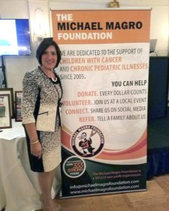 Terrie Magro stands next to a poster touting the Michael Magro Foundation. It was founded in memory of her 13-year-old son, a victim of cancer.