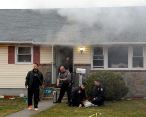 This was the scene at the Georgia Street home of Noah and Jita Klat in Hicksville on Jan. 26 after a fire broke out in the kitchen. Nassau County Police Department Medic Benjamin Butt (in grey shirt) will shortly administer oxygen to the Klat's dog, Inca, being tended by police officers Andrew Massa (kneeling and looking at camera) and Steven Tornetta, who drove Inca to the nearest veterinarian. In the doorway is Hicksville firefighter and ex-Captain Joseph DiFronzo, who helped rescue two other dogs, hiding under a table in the kitchen. The male at left is an unidentified neighbor. (Photo by Kevin Imm)